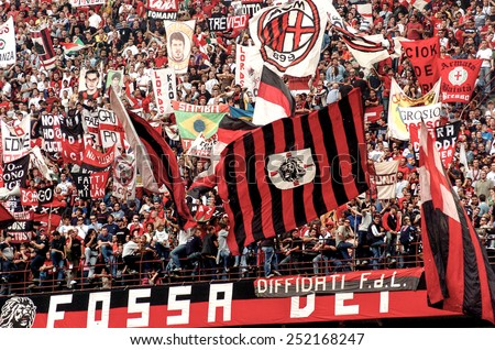 MILAN, ITALY-OCTOBER 11, 2005: AC Milan soccer fans waving flags during the soccer match AC Milan vs FC Internazionale, in Milan. - stock photo