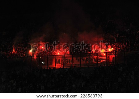 MILAN, ITALY-OCTOBER 23, 2014: french soccer fans lighting smoke flares at san siro stadium, during the Europa League match FC Internazionale vs ST Etienne, in Milan. - stock photo