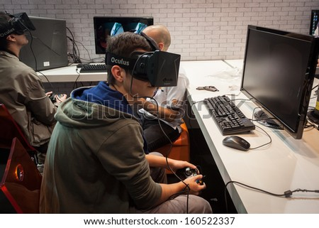 MILAN, ITALY - OCTOBER 26: Guys try a virtual reality headset at Games Week 2013, event dedicated to video games and electronic entertainment on OCTOBER 26, 2013 in Milan. - stock photo