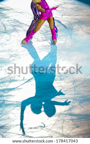MILAN, ITALY-OCTOBER 11, 2008: Shadow on ice of a figure ice skaters couple competing on the Ice Christmas Gala at the Forum arena of Milan. - stock photo
