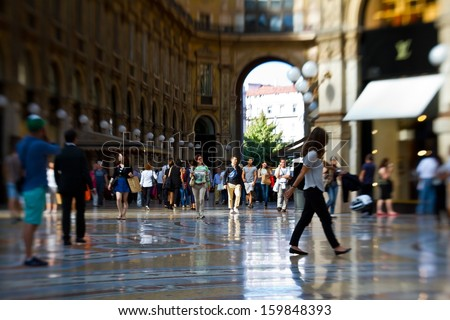 MILAN, ITALY - SEPTEMBER 12: People walk through Galleria Vittorio Emanuele II on September 12, 2013 in Milan. This shopping mall was designed and built by Giuseppe Mengoni between 1865 and 1877. - stock photo