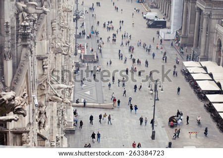 MILAN, ITALY - SEPTEMBER 21, 2014: View from Duomo Cathedral roof - people walking by the street and Piazza Duomo - stock photo