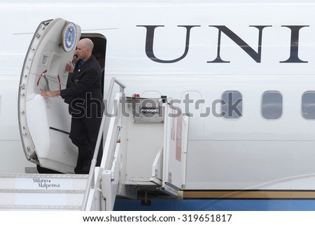 MILAN MALPENSA - JUNE 16, 2015: A functionary of american government opens the hold door of the presidential aircraft (Air Force Two) few moments before the exit of Michelle Obama. - stock photo