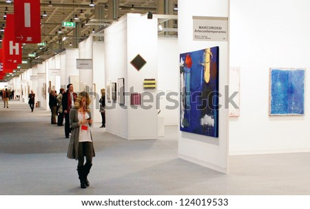 MILAN - MARCH 27: A woman walking trough paintings galleries at MiArt ArtNow, international exhibition of modern and contemporary art March 27, 2010 in Milan, Italy. - stock photo
