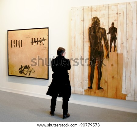 MILAN - MARCH 27: An unidentified person looks at paintings at MiArt ArtNow, international exhibition of modern and contemporary art March 27, 2010 in Milan, Italy. - stock photo