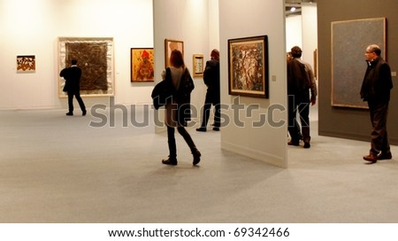 MILAN - MARCH 27: People look at painting and sculptures galleries during MiArt ArtNow, international exhibition of modern and contemporary art March 27, 2010 in Milan, Italy. - stock photo