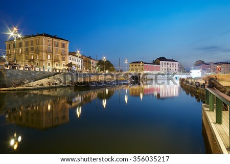 Milan new Darsena, redeveloped docks area in the night, people walking and chatting in Milan, Italy. The Darsena, the canal port was closed since 1979. - stock photo