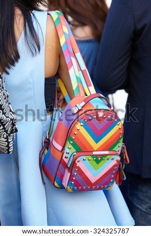 MILAN - SEPTEMBER 24: Woman poses before Cristiano Burani show with colorful backpack during Milan Fashion Week Day 2, Spring / Summer 2016 street style on September 24, 2015 in Milan. - stock photo