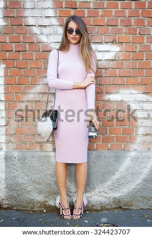 MILAN - SEPTEMBER 24: Woman poses for photographers before Fendi show With Chanel bag and phone cover during Milan Fashion Week Day 2, Spring / Summer 2016 street style on September 24, 2015 in Milan. - stock photo