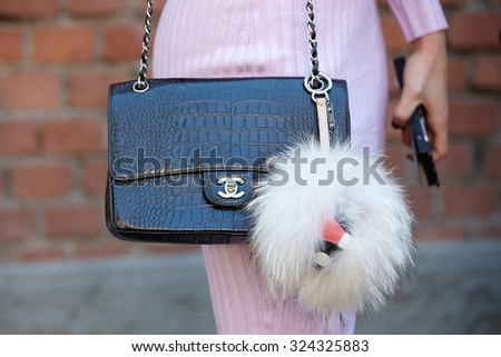 MILAN - SEPTEMBER 24: Woman poses for photographers before Fendi show with Chanel crocodile bag during Milan Fashion Week Day 2, Spring / Summer 2016 street style on September 24, 2015 in Milan. - stock photo