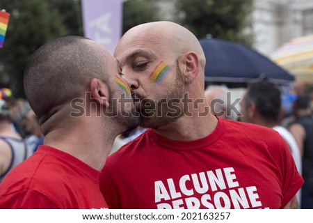 MILANO-ITALY,JUNE 28,2014:An unidentified gays kissing during in eleventh Pride Week Day. Crowd of people participate in the eleventh parade celebrates gays, lesbians  - stock photo