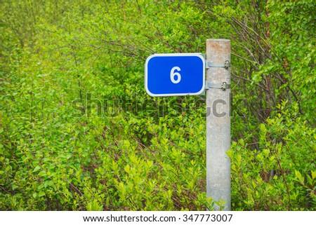 Milepost mileage kilometrs on the roadside  in the bushes - stock photo