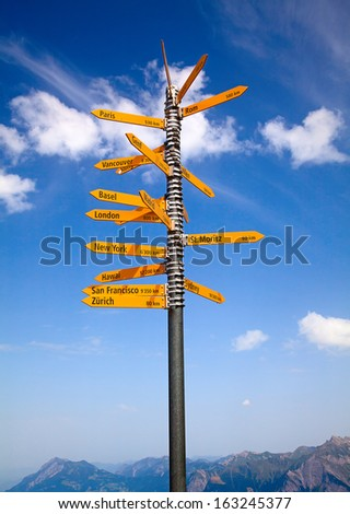 Milestone in the swiss alps, showing distances to major cities - stock photo