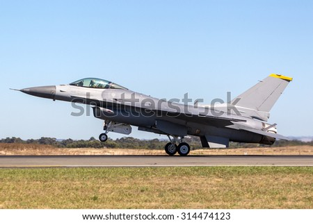 Military aircraft landing on a runway - stock photo