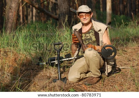Military archeology. Man with metal detector and Soviet WWII 82-mm mortar-shell. Eastern Europe - stock photo
