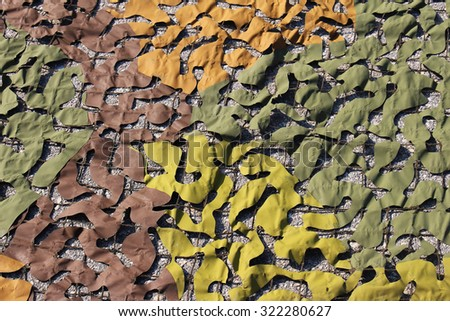 Military camouflage net pattern with green and brown material - stock photo