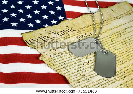 military dog tags on American constitution with flag background - stock photo