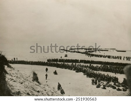 Military evacuation of Dunkirk during World War 2. Thousands of British and French troops wait on the dunes of Dunkirk beach for transport to England. May 26-June 4, 1940. - stock photo