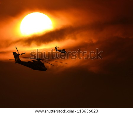 Military helicopters silhouette flying against sun - stock photo