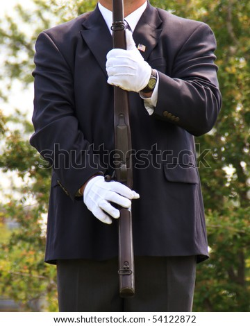 Military Honor Guard presenting Arms after twenty one gun solute. Man is wearing white gloves and Civilian suit and tie, with an American Flag pin in his lapel. Ceremonial Guard - stock photo