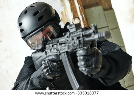 military industry. Portrait of special forces or anti-terrorist police soldier, private contractor armed with assault rifle ready to attack during clean-up operation, mission - stock photo