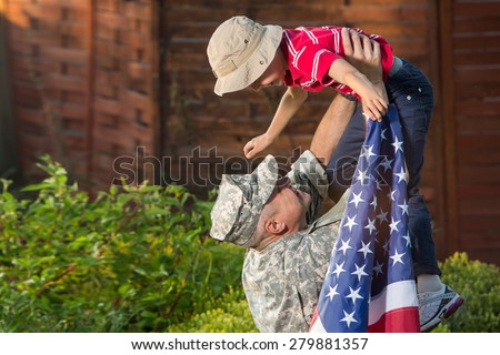 Military man father hugs son. Portrait of happy american family, daylight, shadow on boys face - stock photo