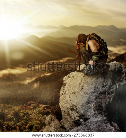 Military man warrior praying before the fight and sitting on a rock on summer morning - stock photo