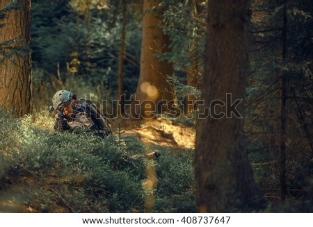 Military Operation in Forest. Soldier with Assault Rifle Laying Covered and Spotting Enemy. Military Concept. - stock photo