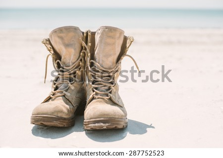 military or hiking boots in the sand. Bright sun and space to photo - stock photo