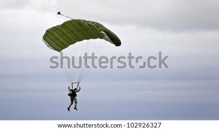 Military parachutist on the background of dark sky - stock photo