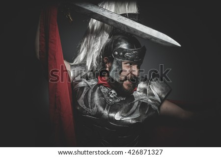 Military, Praetorian Roman legionary and red cloak, armor and sword in war attitude - stock photo