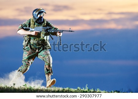 military. soldier in uniform running with machine gun weapon on sunset during attack outdoors. Authentic shooting in challenging conditions. Maybe little blurred. - stock photo