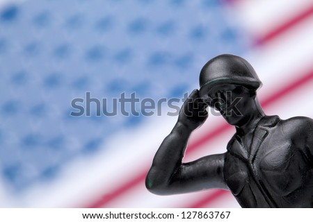Military Soldier saluting and giving honor on American flag - stock photo