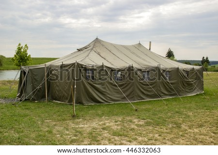 military tent in the the open countryside meadow - stock photo
