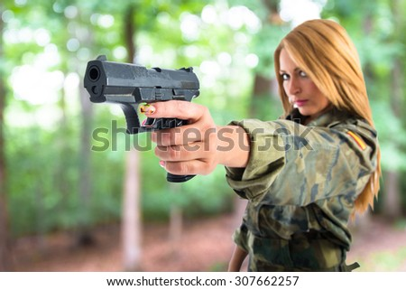 military woman shooting a gun on unfocused background - stock photo