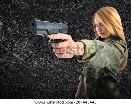 military woman shooting a gun over textured background - stock photo