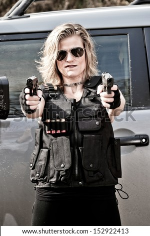 Military Woman wearing Tactical Gear and Holding two guns - stock photo