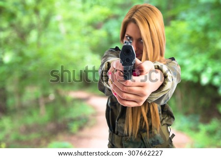 Military woman with gun on unfocused background - stock photo