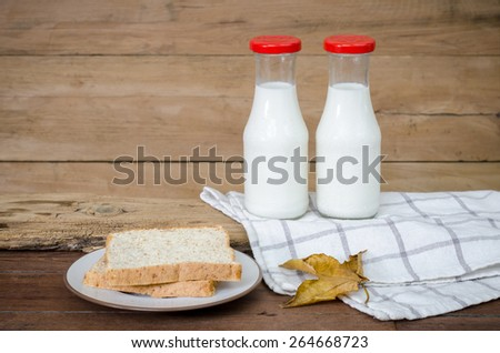 Milk and bread put on old wood. - stock photo