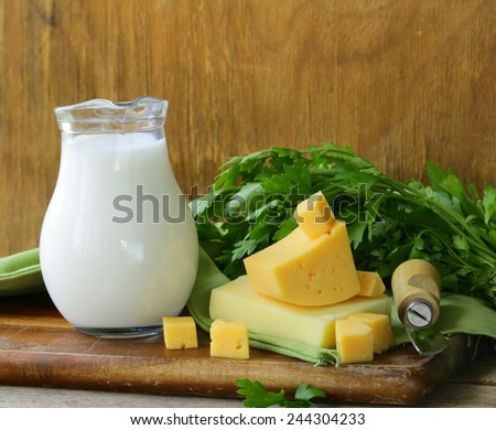 milk and cheese on a wooden table, rustic style - stock photo