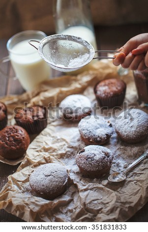 Milk and chocolate cupcakes on wooden background. Little girl sprinkle with powdered sugar - stock photo