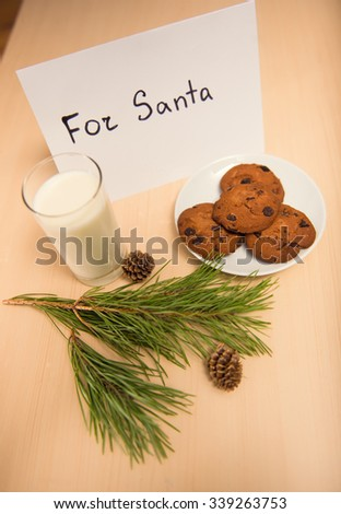 Milk and cookies for Santa on the table. Celebrating Christmas - stock photo