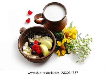 Milk and curd with summer fruits in brown ceramic bowls, isolated on a white background - stock photo