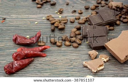 Milk and dark chocolate, chili peppers and cayenne, coffee beans on a rustic wooden surface. Chocolate bar - stock photo