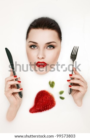 Milk and strawberry. Beautiful woman with fork and knife in hands. - stock photo