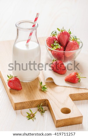 Milk and strawberry on white wooden background - stock photo