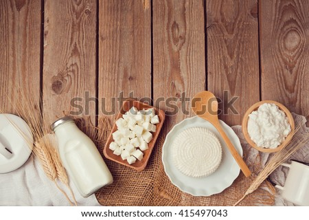 Milk bottle and cheese on wooden table. Healthy eating concept. View from above. Flat lay - stock photo