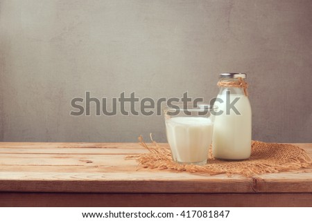 Milk bottle and milk glass on wooden table. Healthy eating concept - stock photo
