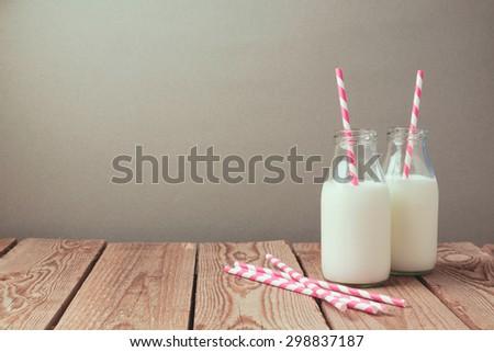 Milk bottles with retro striped straws on wooden table - stock photo