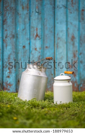 Milk cans on wood vintage background - stock photo